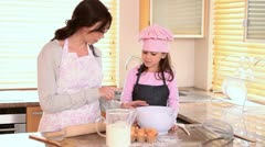Mother helping her daughter to cook Stock Footage