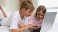 Cheerful siblings using a laptop Stock Footage