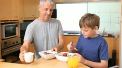 Father and son eating their breakfast together Stock Footage