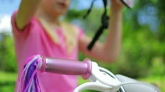 Girl puts on a pink cycling helmet and fastens the clasps Stock Footage