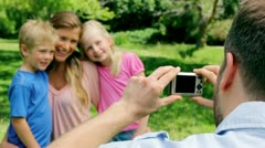Mother and her children pose for a picture being taken by the father Stock Footage