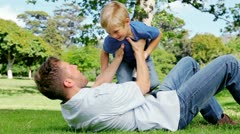 Father lies on the grass and raises his son in the air as he pretends to be and Stock Footage