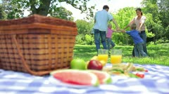 Family dancing in a cirlcle in the background with a platter on a picnic basket Stock Footage