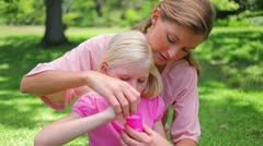 A mother helps her daugther to blow bubbles Stock Footage
