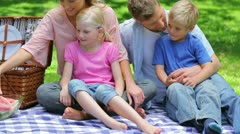A mother handing a slice of watermelon each to her children and a sandwich to Stock Footage