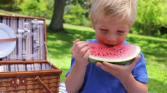 A boy looks at the camera while biting a watermelon before swallowing and - stock footage