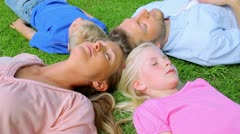 A family lies head to head in grass while sleeping before the daughter begins to Stock Footage
