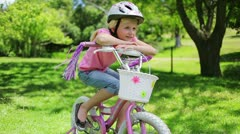 A girl sits on a bike while leaning on the handlebars as its tassels blow in the Stock Footage