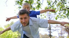 A father sways from side to side while giving his son a piggy back with his arms Stock Footage