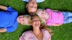 Overhead shot of a family smiling as they lie head to head in grass - stock footage