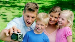 Father takes a picture of himself and his family before looking at the picture Stock Footage