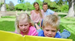 Two kids reading a book together while smiling and looking at each other as they Stock Footage