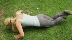 A woman doing push-ups with her feet crossed Stock Footage