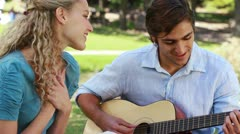 Boyfriend plays the guitar for his girlfriend Stock Footage
