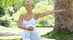Woman performing a yoga position in the park Stock Footage