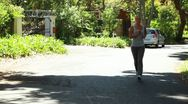 Jogging woman runs down the street with the camera in front of her Stock Footage