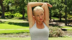 Woman stretching her arms and then looking at the camera and smiling Stock Footage