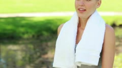 A woman walks in the park and takes a drink as she rests from training Stock Footage