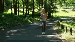 A woman jogs in the park and then is jogging on a main road afterwards Stock Footage