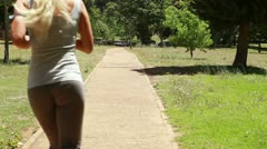 Stock Video Footage of Jogging woman runs down the footpath
