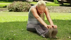 A woman stretches out in the park Stock Footage