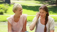 Two girls sit in the park and pass the phone back and forth while talking on it Stock Footage