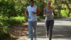 Stock Video Footage of A jogging couple run together down the street