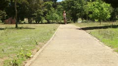 A woman jogs up a footpath towards and past the camera Stock Footage