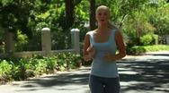 A woman jogs down the street as she looks to the side Stock Footage