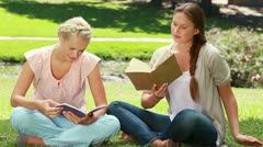 Two women read books in the park as one shows her friend her book and they laugh Stock Footage