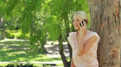 A woman standing by a tree talking on her phone as she hangs up at looks at the Stock Footage