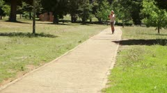 Stock Video Footage of A woman jogs up a footpath past the camera