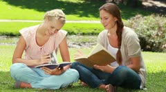 Two ladies reading in the park as they then look at the camera Stock Footage