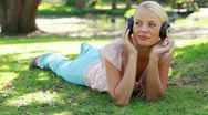 A woman moves her head to the rhythm of the music as she listens to headphones Stock Footage