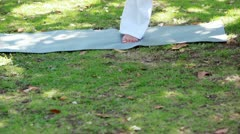 A woman in the park performing yoga Stock Footage