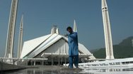 A man cleans tiles in front of the Faisal Mosque, Islamabad Stock Footage