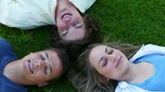 Three friends lying head to head before opening their eyes and smiling Stock Footage
