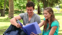 Two friends laughing while pointing at a folder as they sit together Stock Footage