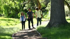 Three friends talking to each other as they walk on a park trail Stock Footage