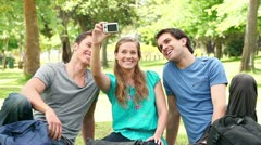 Three friends posing as they take a photo of themselves before laughing Stock Footage