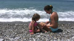 The young woman and child looking starfish on a beach  00073-natasha anna sea Stock Footage