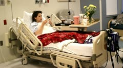Patient eating in hospital bed and watching TV Stock Footage