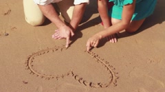 Couple drawing a heart shape in the sand HD Stock Footage