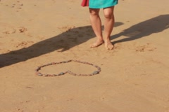 Couple destroying heart shape made of stones on the sand NTSC Stock Footage