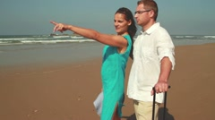 Young happy couple with valise standing on the beach, steadicam shot HD Stock Footage