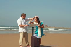 Couple with valise having fight over map on the beach, steadicam shot NTSC Stock Footage