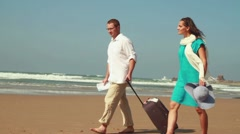 Couple with valise looking at map on the beach, slow motion, steadicam shot Stock Footage