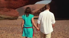 Couple in love walking on Legzira beach, steadicam shot HD Stock Footage