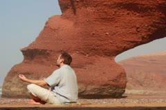 Man meditating on Legzira beach NTSC Stock Footage