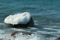Waves over Ice Capped Boulder NTSC Stock Footage